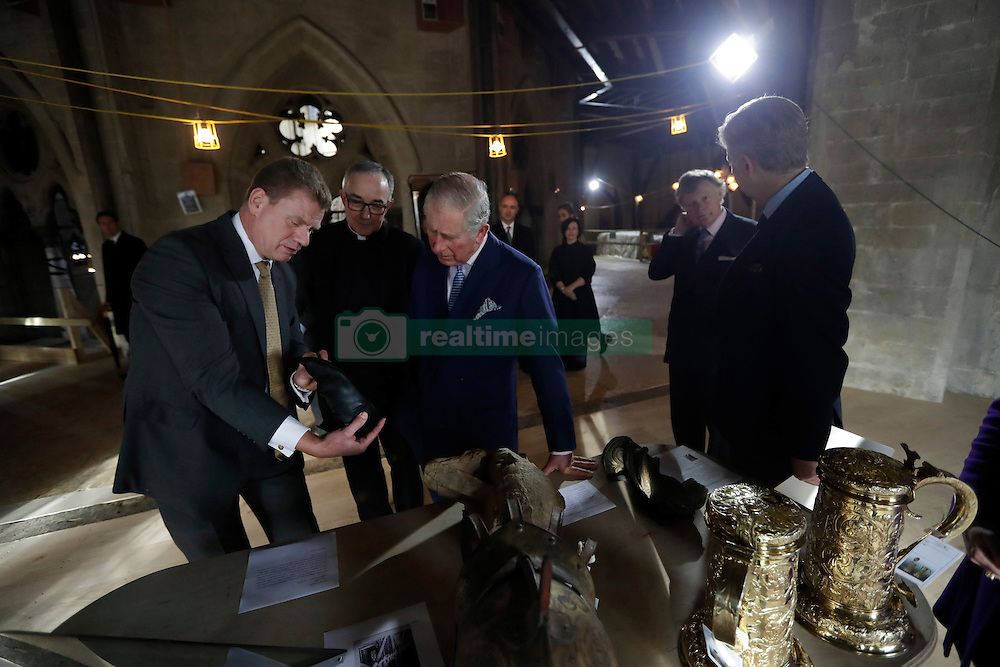 The Prince of Wales is shown a monk's shoe and other artefacts by Dr Tony Trowles (left) the head of collections, flanked by the Dean of Westminster John Hall during his visit to the The Queen's Diamond Jubilee Galleries at Westminster Abbey in London.