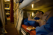 Vinnie Browse switches off his overhead reading light in his Junior Rating bunk aboard HMS Vigilant, a 16,000 ton, 150m long Vanguard class nuclear submarine while moored at HM Naval Base Clyde, Faslane, Scotland. Vigilant has a crew of 140 men and when at sea, only incoming communication, family-grams, are allowed so many months away on operational duty can be tough on home life. On-board entertainment is therefore important for morale. The Vanguard Class SSBN (Ship Submersible Ballistic Nuclear) provides the United Kingdom's strategic nuclear deterrent and carries Trident II ballistic missiles, powered by a pressurised water reactor (PWR) fuelled by a ton of fissionable uranium elements producing huge amounts of energy. Image taken for the 'UK at Home' book project published 2008.
