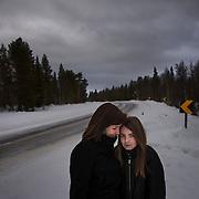 """Kuvattu 27.2.2015 Irina ja Tinja Hakovirta Tinjan syntymäpaikalla.<br /> Peurasuvannon mutka<br /> Matkaa keskussairaalaan: 182 km<br /> 28.4.2004, <br /> puoli kolmen aikaan yöllä<br /> <br /> Irina Hakovirta: """"Peurasuvannon kahvilan kohdalla minusta alkoi tuntua, että pää vain tulee ulos. Aloin karjua kuskille, että pysäytä, pysäytä. Vauhtia oli varmaan 120 kilometriä tunnissa, eikä sillalle voinut pysähtyä. Oli jo keväistä, mutta tiellä oli liukasta mustaa jäätä. Heti sillan jälkeen on tiukka mutka, ja kuski joutui jarruttamaan tienhaaraan.<br /> <br /> Jälkeenpäin mietin, että mitä jos jotain olisi sattunut. Tinja syntyi puoli kolmelta yöllä, eikä tiellä ollut mitään liikennettä. Peurasuvannon lähellä ei ole taloja. Synnytys oli niin hallitsematon, että pelkäsin etukäteen seuraavaa.""""<br /> <br /> Ivalossa oli oma synnytysosasto vuoteen 1999 asti. Kun se lakkautettiin, pitenivät Inarin ja Utsjoen kuntien äitien synnytysmatkat 200–500 kilometriä. Matka Rovaniemelle on pitkä ja moni synnytys joudutaan tekemään ambulanssissa matkan varrella.<br /> <br /> Irina and Tinja Hakovirta in the place of Tinja's birth<br /> Peurasuvanto<br /> Distance to hospital: 182 km<br /> 28.4.2004, <br /> 2:30 AM<br /> <br /> Labour ward in Ivalo was closed in 1999. After that the distance to the nearest labour ward in Rovaniemi is 200 to 500 kilometers. Some of the babies are born on the road."""