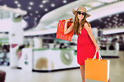 Young woman in her twenties in summer dress out shopping in the mall with shopping bags