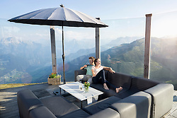 Young couple drinking wine on terrace, Zillertal, Tyrol, Austria