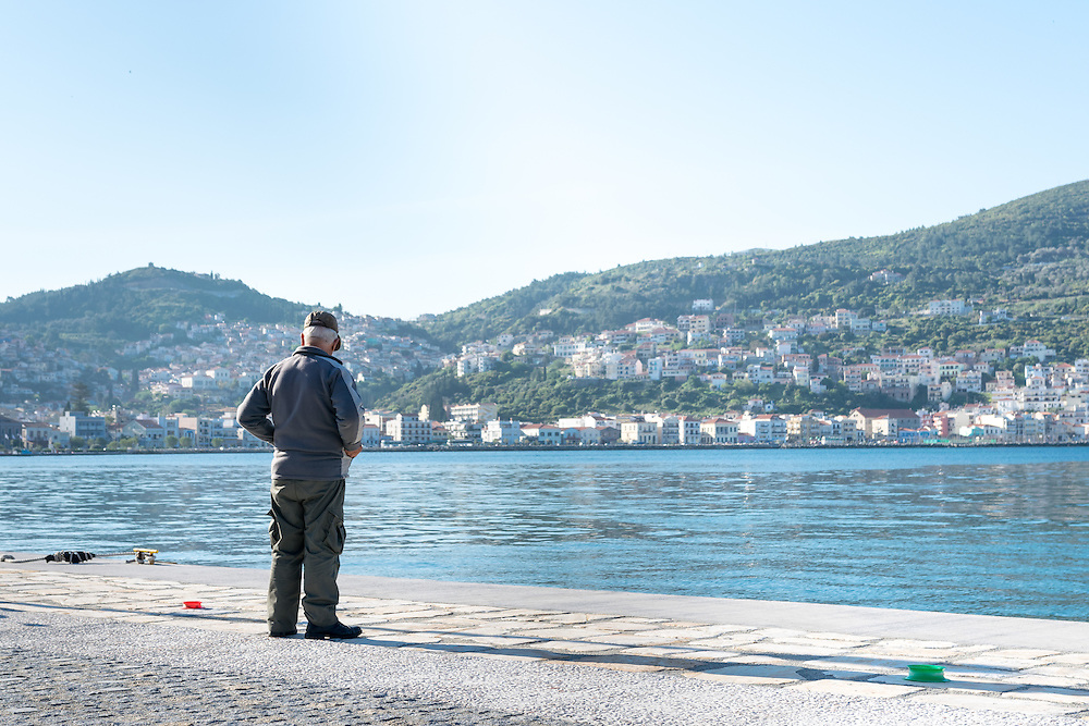 13 April 2016: The Greek Island of Samos, where all refugees have been moved to a closed camp, so-called hotspot, where they are kept awaiting registration, identification, and transfer for resettlement in a European country. Many refugees stay for weeks or even several months awaiting resettlement. Refugees and volunteer workers report lack of information, long lines for food, and poor nutrition. On the shore of the town, life is now in many ways back to normal. Here, an elderly man fishing on the shore by the dock.
