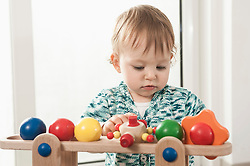 Baby girl concentrating playing toy wooden
