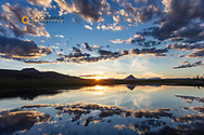 Sunset clouds reflect into wetlands along the Rocky Mountain Front with Haystack Butte near Augusta, Montana, USA