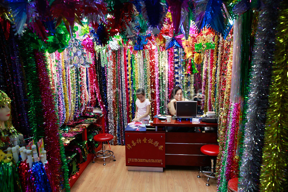 A woman and her daughter wait in their stall selling Christmas decorations at the Yiwu International Trade City in Yiwu, Zhejiang Province, China on Sunday, 11 September 2011.   As the trading hub for small and medium manufacturers and exporters in the Yangtze River Delta region, Yiwu faces an uncertain future as export orders decline due to the slow economic recoveries of China's two largest trading partners, Europe and the United States