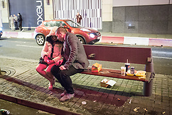 © Licensed to London News Pictures . 01/01/2014 . Manchester , UK . A man and a woman sit on a bench littered with fast food debris .  Revellers see in the New Year in Manchester today (January 1st 2014) as police report that officers are at full stretch responding to calls . Photo credit : Joel Goodman/LNP