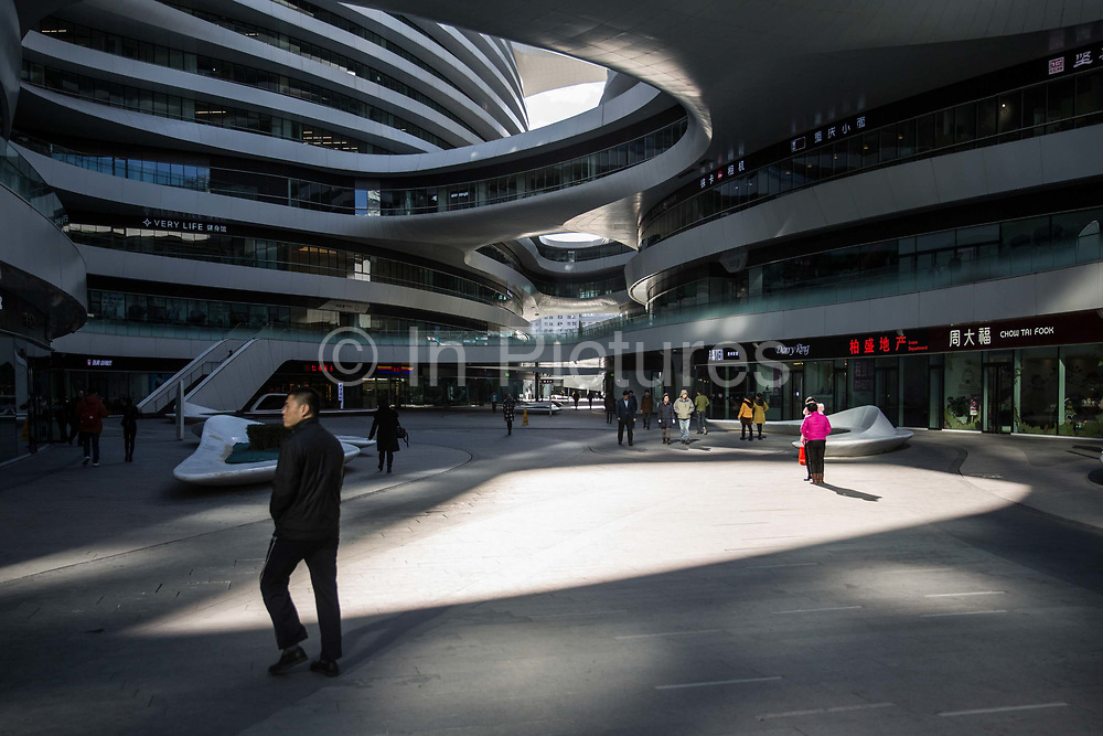 People walk through the atrium of Soho Galaxy, a Zaha Hadid designed mix-use complex in Beijing, China, on Tuesday, Dec. 01, 2015.