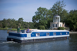 © Licensed to London News Pictures. 15/06/2021. Henley-on-Thames, UK. A barge makes its way along the River Thames at Henley-on-Thames in Oxfordshire on a hot summer's morning. Photo credit: Ben Cawthra/LNP