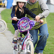 April 18, 2009 -- BATH, Maine. Older brother Judah Merrill, 12, of Bath, teaches his sister Lydia, 8, how to ride a bike in Library Park in Bath on Saturday afternoon.  Photo by Roger S. Duncan.