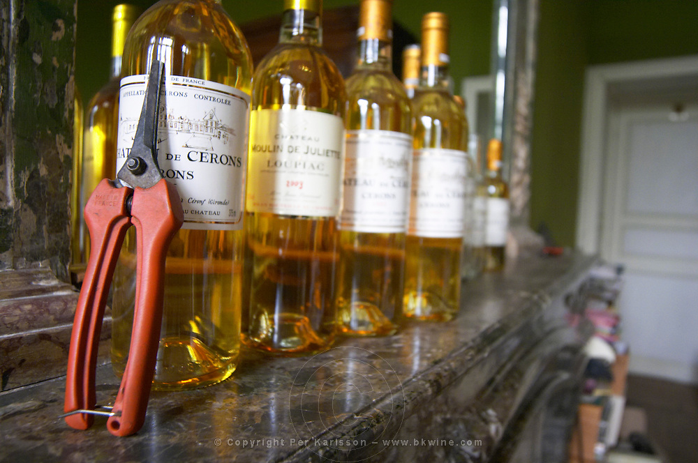 Bottles on a marble shelf above the fire place with sauternes wine: Chatea de Cerons, Chateau Moulin de Juliet, Loupiac and others. A secateur used for harvesting the wine. Chateau de Cerons (Cérons) Sauternes Gironde Aquitaine France