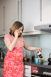 Pregnant woman talking on smartphone and making coffee for breakfast in the kitchen, Munich, Bavaria, Germany