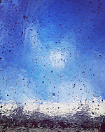 Textural abstract of a blue sky through old bubbled and wavy glass