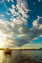 Big Billowing Clouds Cut Off The Setting Sunlight As A Boat Crosses Over From Light To Shade on Lake Minnetonka
