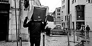 Lisbon, Portugal - <br /> A man uses a card box to protect himself from the rain, in Intendente, center Lisbon. This photo is part of an one week reportage on Portuguese Daily Life, between Dec 17 and Dec 21, 2012, on the year that the austerity measures set by the Portuguese Government to achieve the goals set by the Troika (IMF, ECB, EC) for the Portuguese Bailout Package, result in the highest unemployment rates ever since the beginning of Portuguese Democracy (1974) and poverty starts to show on the former middle class families.<br /> Photo Credit: Pedro Nunes/4SEE