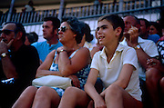 A mother and adolescent watch the bullfighting while on a daytrip to Malaga on the Costa del Sol, southern Spain. While the boy looks amused, his mother looks nervous at the spectacle below in the bullfighting ring in the centre of town. The 70s saw an explosion of UK tourism to the Spanish costas, providing middle and working class with affordable holidays, a few hours flying time from Britain.