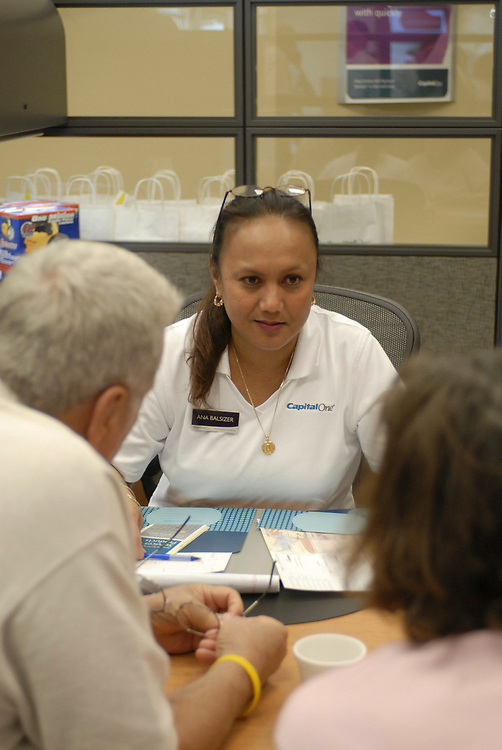 Austin, TX August 1, 2006: Grand opening event for a Capital One banking center branch bank in south Austin, TX in a growing suburban area.  A customer service representative (CSR) helps a customer open an account.  <br /> ©Bob Daemmrich /