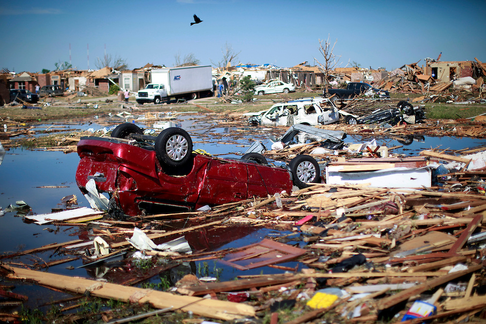 A bird flies over destroyed cars of teachers lying in the pond next to Briarwood elementary school in Oklahoma City, Oklahoma May 22, 2013.  Rescue workers with sniffer dogs picked through the ruins on Wednesday to ensure no survivors remained buried after a deadly tornado left thousands homeless and trying to salvage what was left of their belongings. Curvature of horizon in the photo is due to an ultra-wide angle lens.  REUTERS/Rick Wilking (UNITED STATES)