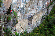 A view of the Inca Bridge at the ancient site of Machu Pichu in the Cusco region of Peru. The bridge is part of a trail that heads west out of Machu Pichu. To prevent outsiders from entering Machu Pichu on this trail, a 20-foot gap was left in this section of the carved cliff edge over a sheer drop. Two tree trunks could be used the bridge the gap which was otherwise impassable.