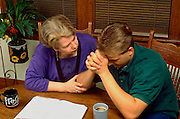Aunt and nephew age 56 and 23 working on personal problem with Bible.  St Paul Minnesota USA