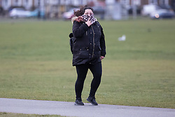 © Licensed to London News Pictures. 11/03/2021. London, UK. A woman holds onto her scarf as she walks on a windy Blackheath Common in South East London. A yellow weather warning for wind is in place in parts of the UK. Photo credit: George Cracknell Wright/LNP