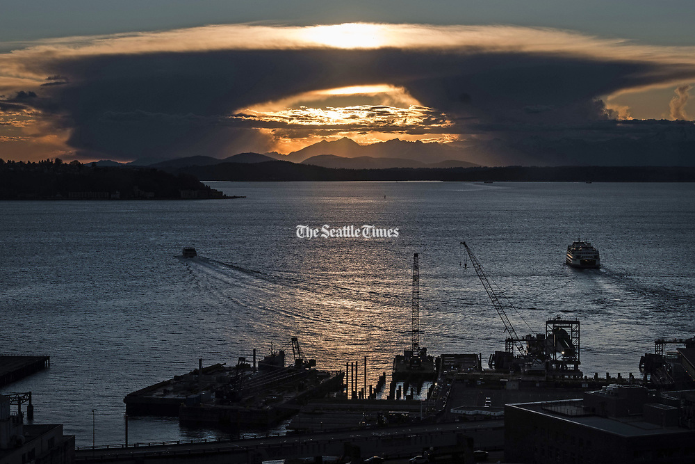 A cloud formation creates a tunnel by which to view the Olympic Mountain range in this view from Smith Tower. (Dean Rutz / The Seattle Times)