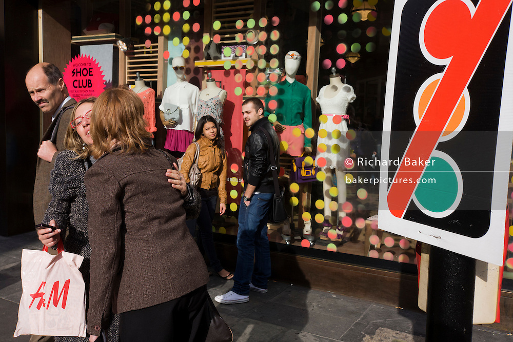 Girfriends greet other outside the spotted shop window of Urban Outfitters in central London.