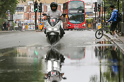 © Licensed to London News Pictures. 27/07/2019. London, UK. A motorbike rides through a flood on Green Lanes in north London, caused by heavy overnight downpour. Photo credit: Dinendra Haria/LNP