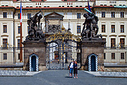 "A couple is doing a ""selfie"" in-front of the Wrestling Titans (Sousoší Souboj Titánů) infront of empty Prague Castle at ""Hradcany Square"" (Hradcanske Namesti). The Czech government lowered the security measures and as of Monday 25 May 2020, wearing of protective masks will be mandatory only in the interiors of buildings other than the place of residence and in public transport."