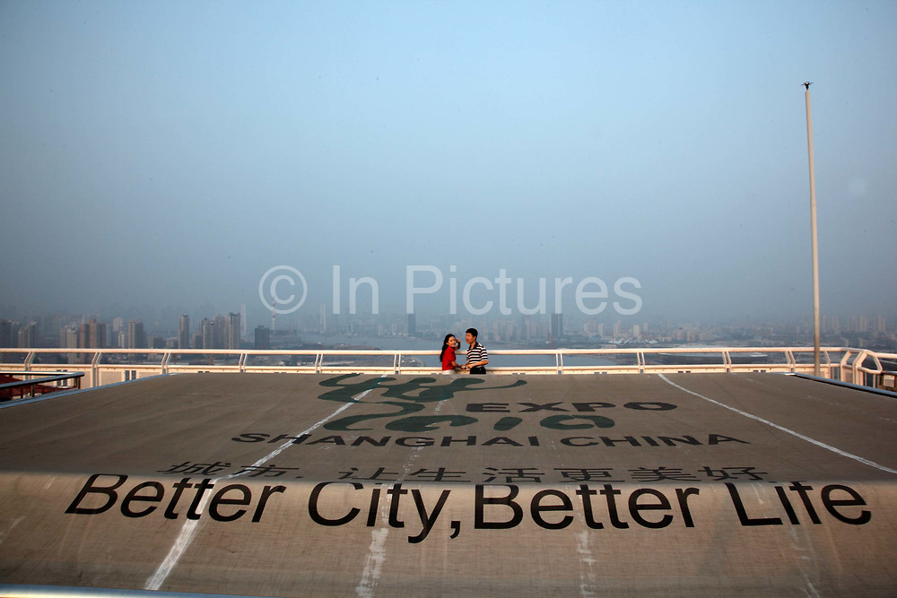 A couple stands on a bridge overlooking the 2010 World Expo site in Shanghai, China on 26 August 2009. The Shanghai World Expo will eventually see a record breaking 70 million visitors during its six months duration.