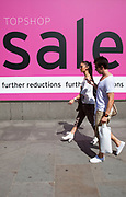 Shoppers walk past a large pink Sale sign outside Topshop in central London. It's time for the summer sales, and most shops are advertising big reductions in prices. Bargains are avaiable and the shopping streets are busy.