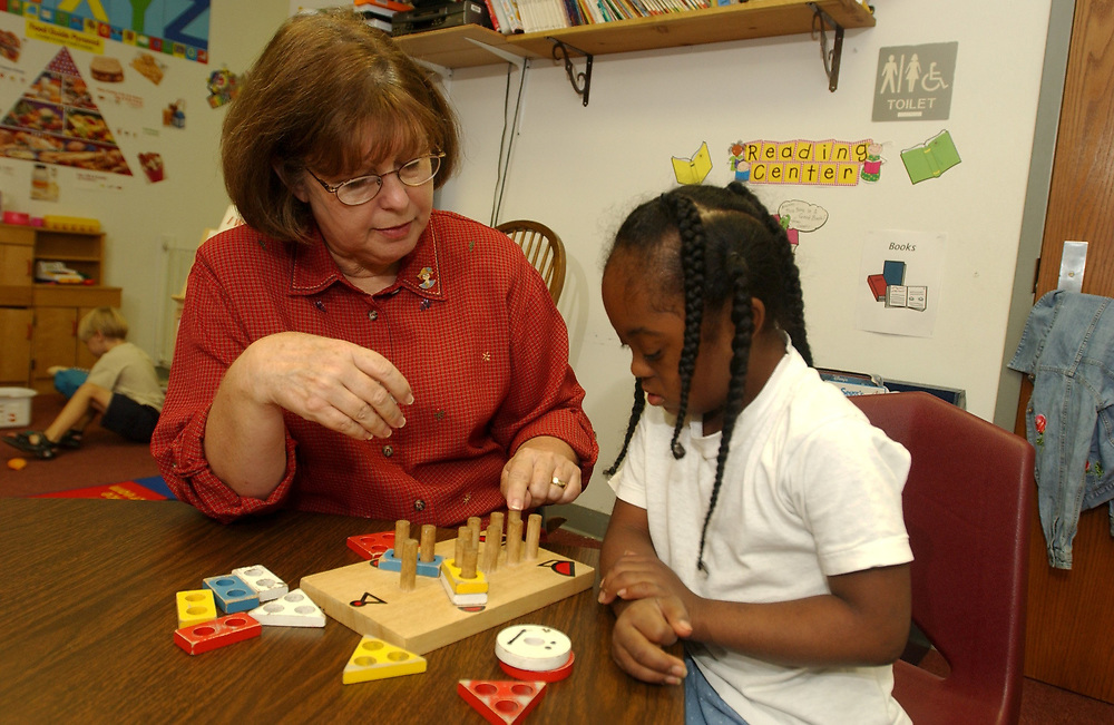 Gun Barrel City, Texas September 9, 2003:   Education at Lakeview and Southside Elementary Schools in the Mabank Independent School Discrict in northeast Texas. <br /> MODEL RELEASE SP63 (student) and SP69 (teacher). Nine-year-old African-American student with Down's Syndrome, learning academic skills, counting, and learning shapes and colors.  She's small for her age due to a heart condition at birth. <br /> ©Bob Daemmrich