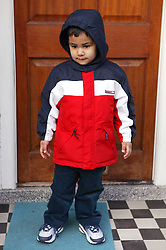 Young boy standing outside the front door of his house,