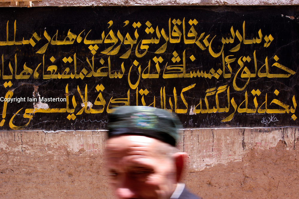 Muslim man walks past a sign with Arabic writing in the old town of Kashgar in Xinjiang Province of China