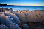 The Pancake Rocks, located in Punakaiki on the West Coast of New Zealand, are layered columns of limestone, somewhat resembling stacks of pancakes. Geologists are not certain of their origin. New Zealand's Southern Alps are visible on the horizon.