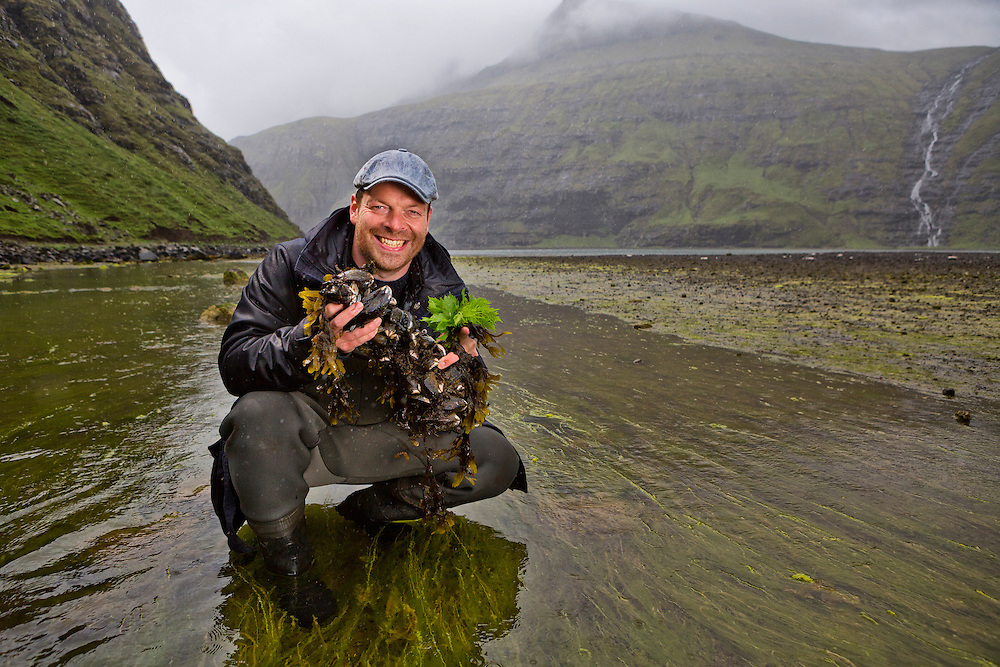 Saksun Lake, Streymoy Island, Faroe Islands<br /> <br /> Gutti Winther, a famous Faroese chef, believes in using nature in his cooking.  Here he holds blue mussels found in Saksun lake.  He prepares the mussels with fresh sorrel and Angelika which he has picked along the road on his way to the lake.  Gutti travels with a burner and some basic cooking necessities in the back of his car so he doesn't have to go far to cook an amazing meal, with an amazing view.
