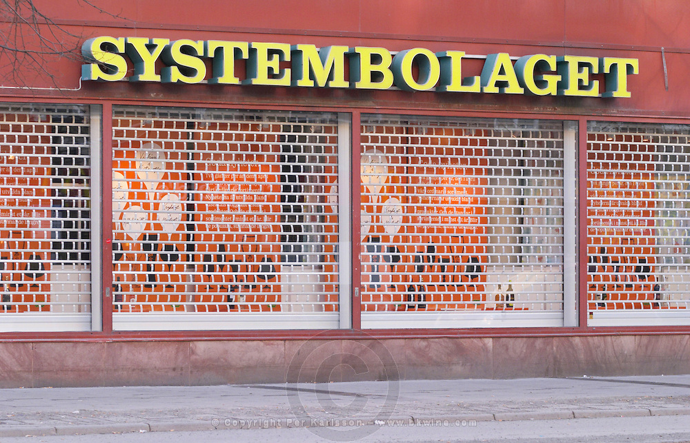 The front of one of the Systembolaget shops, the retail monopoly for selling alcohol wine beer and spirits, with a yellow neon sign and the iron wire curtain closed on Soder in the shopping centre Ringen Stockholm, Sweden, Sverige, Europe