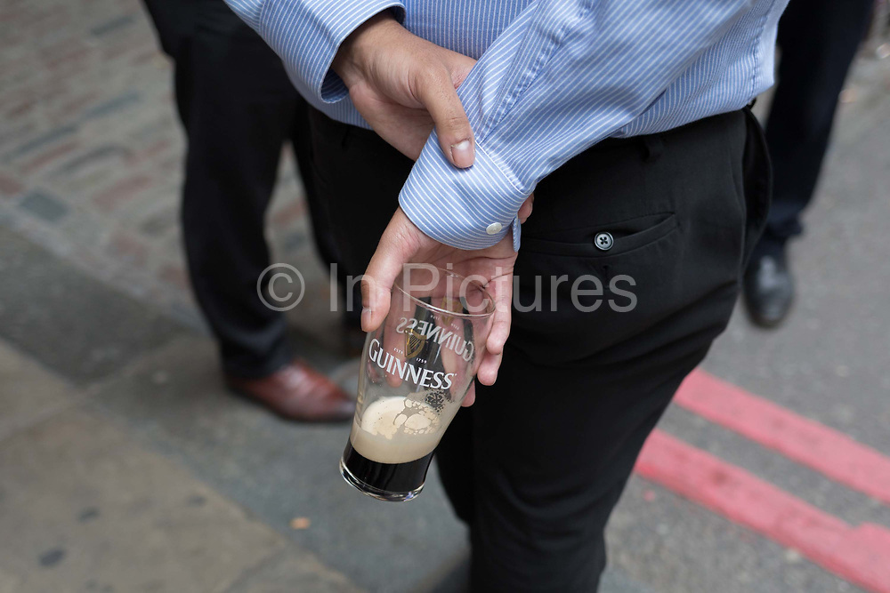 As heatwave temperatures climb to record levels - the hottest day of the year so far, a city worker holds an almost-finished pint of Guinness behind his back in the City of London, on 25th July 2019, in London, England.
