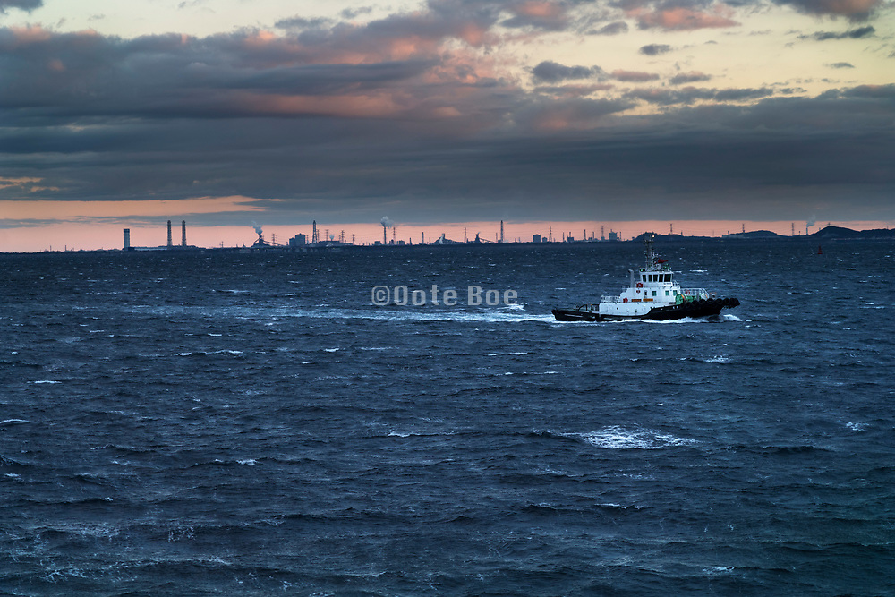 tugboat in Tokyo Bay with the Chiba prefecture heavy industry in the background Early morning Japan
