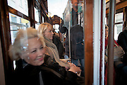 Some tourists and local passengers enjoy a trip in a Lisbon's nº28 yellow tram, through the central, most historic region of the city.