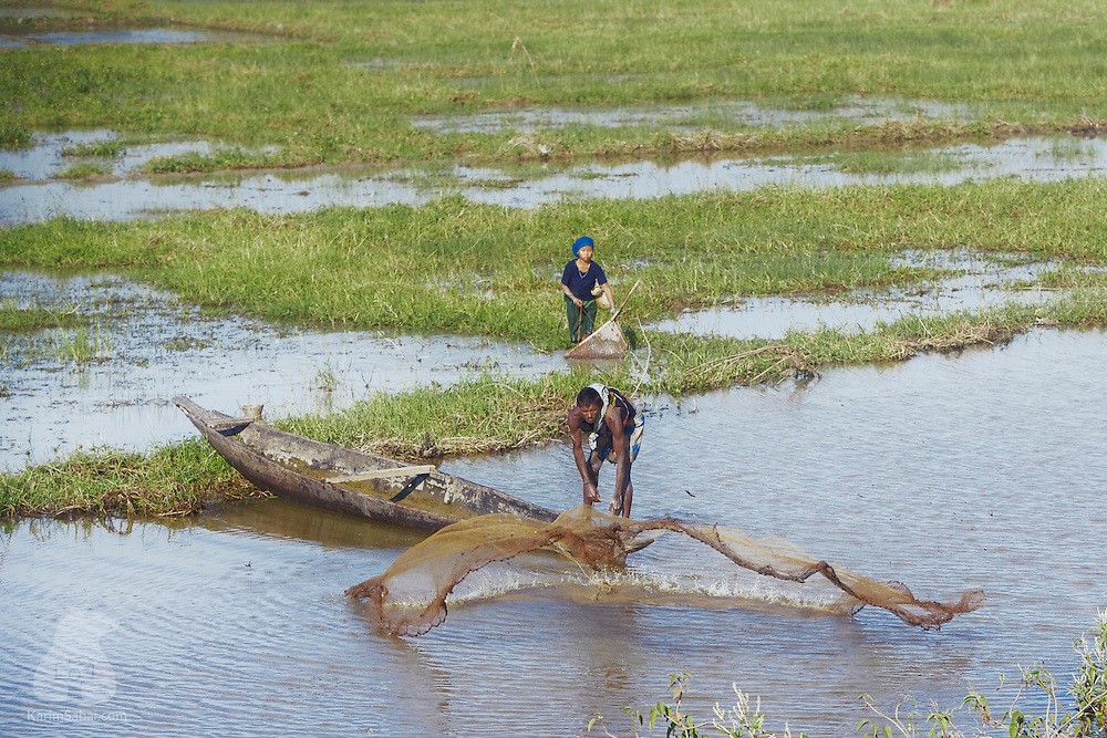 Assam, India. A fisherman casts his fishing net in the shallow waters neighboring a rice paddy while a young bodo woman uses a different fishing technique involving a woven straw basket and a clay storage bucket.