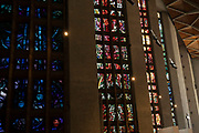 Interior of Coventry Cathedral also known as St Michaels, a modern cathedral founded in 1956 and well known for having stunning modernist stained glass, minimalist structure and large scale tapestry on 23rd June 2021 in Coventry, United Kingdom. The Cathedral Church of Saint Michael, commonly known as Coventry Cathedral, is the seat of the Bishop of Coventry and the Diocese of Coventry within the Church of England. The current St Michaels Cathedral, built next to the remains of the old, was designed by Basil Spence and Arup, built by John Laing and is a Grade I listed building.