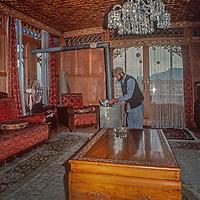A housekeeper cleans a tourist houseboat  on Dal Lake, Srinigar, Kashmir, India.