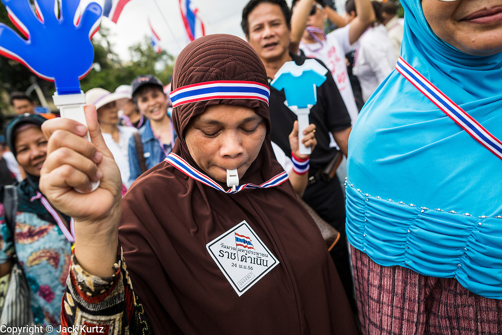 24 NOVEMBER 2013 - BANGKOK, THAILAND:     A Muslim anti-government protestor blows a whistle to make noise during a protest on Rathchdamnoen Ave in Bangkok. More than 400,000 people packed onto Ratchdamnoen Ave in Bangkok Sunday, continuing an anti-government protest that started weeks ago over a blanket amnesty bill passed by the Thai Parliament. The amnesty bill was defeated in the Thai Senate and the protest morphed into a general protest against the government. The protestors are allied with the Thai Democrat party, the opposition party in parliament. Tens of thousands of pro-government Red Shirts have come to Bangkok to defend the government and are rallying in a different part of the city. Police have warned of clashes between the two groups but as of Sunday evening no problems had been reported. The protestors allege that the amnesty would allow fugitive former Prime Minister Thaksin Shinawatra to return to Thailand.        PHOTO BY JACK KURTZ