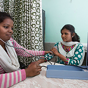CAPTION: Adolescent client Sujata Shit is getting her blood pressure checked. She came to the ARSH clinic complaining of weakness and a spinning head. Most of the girls with anemia have low blood pressure. LOCATION: Adolescent Reproductive and Sexual Health (ARSH) clinic, Ghatshila Community Health Centre (CHC), Purbi Singhbhum (district), Jharkhand (state), India. INDIVIDUAL(S) PHOTOGRAPHED: Sarita Kumari Panna (left) and Sujata Shit (right).