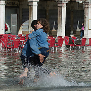 VENICE, ITALY - NOVEMBER 05:  A couple has fun in Saint Mark's Square during today Acqua Alta on November 5, 2013 in Venice, Italy. The high tide, or acqua alta as it is locally known, is a natural event most commonly affecting the city during Autumn and Winter.  (Photo by Marco Secchi/Getty Images)