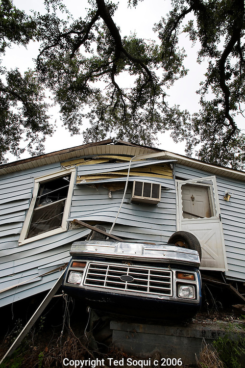 A truck remains crushed beneath a house in the lower 9th Ward of New Orleans one year after Hurricane Katrina. The house was lifted by flood waters after the Industrial canal was breeched.