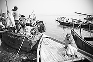 Varanasi, A man sits alone on his boat while the boat behind him overflows. Rendered in a sepia and purple split-tone.