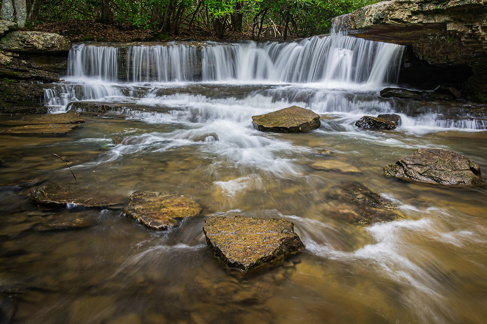 The falls of Mash Fork in Camp Creek State Park, West Virginia gently spill over the rock ledges as the shallow water rushes around the loose rock in the creek bed.