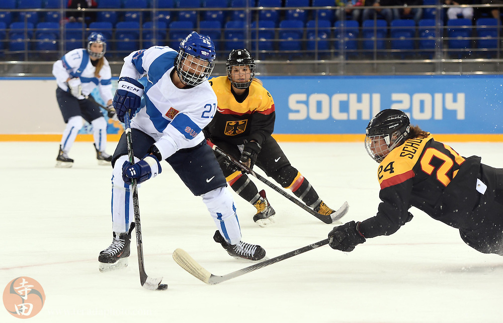 Feb 16, 2014; Sochi, RUSSIA; Finland forward Michelle Karvinen (21) controls the puck against Germany forward Lisa Christine Schuster (24) in the women's ice hockey classifications round during the Sochi 2014 Olympic Winter Games at Shayba Arena.