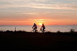 People bicycling at sunset at the beach in Grotta, Iceland - fólk á reiðhjóli við sólsetur við Gróttu